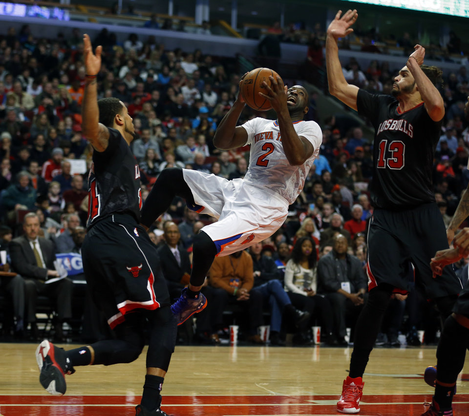Photo - New York Knicks point guard Raymond Felton (2) shoots between Chicago Bulls point guard D.J. Augustin, left, and center Joakim Noah, right, during the first half of an NBA basketball game on Sunday, March 2, 2014, in Chicago. (AP Photo/Jeff Haynes)