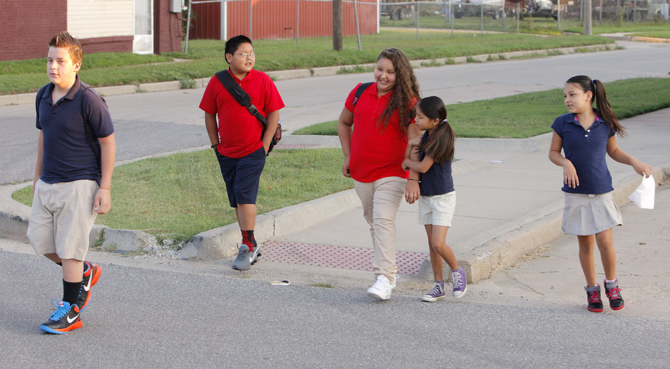 Photo - Students from Mark Twain Elementary walk to a school bus stop at NW 2 Street and Klein Ave. for the first day of school in Oklahoma City Monday, Aug. 4, 2014.  Photo by Paul B. Southerland, The Oklahoman