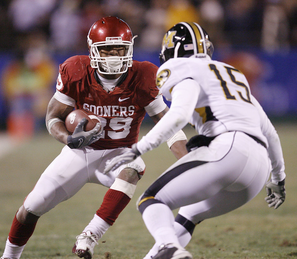 Photo - Oklahoma's Chris Brown (29) looks for running room past Missouri's Del Howard (15) during the first half of the Big 12 Championship college football game between the University of Oklahoma Sooners (OU) and the University of Missouri Tigers (MU) on Saturday, Dec. 6, 2008, at Arrowhead Stadium in Kansas City, Mo. 