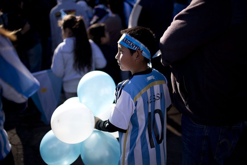 Photo - A fan of Argentina's national soccer team waits to say bye to the bus taking the players to the airport in Buenos Aires, Argentina, Monday, June 9, 2014. Argentina's team is leaving Monday to compete in the Brazil's 2014 soccer Word Cup. (AP Photo/Natacha Pisarenko)