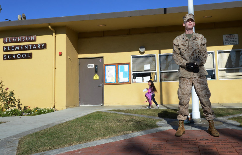 U.S Marine Corps Reserve Sgt. Craig Pusley stands guard as kindergarten student Liset Corona, 5, walks to her class at Hughson Elementary School on Wednesday morning Dec. 19, 2012 in Hughson, Calif. Pusley , a  Marine veteran of Iraq and Afghanistan took up self-imposed duty in front of a central California elementary school in the wake of the Connecticut shooting..  (AP Photo/The Modesto Bee, Ed Crisostomo) LOCAL TV OUT (KXTV10, KCRA3, KOVR13, FOX40, KMAX31, KQCA58, CENTRAL VALLEY TV); LOCAL PRINT OUT (TURLOCK JOURNAL, CERES COURIER, OAKDALE LEADER, MODESTO VIEW, PATTERSON IRRIGATOR, MANTECA BULLETIN, RIPON, RECROD, SONORA UNION DEMOCRAT, AMADOR LEDGER DISPATCH, ESCALON TIMES, CALAVERAS ENTERPRISE, RIVERBANKS NEWS) LOCAL INTERNET OUT (TURLOCK CITY NEWS.COM, MOTHER LODE.COM)