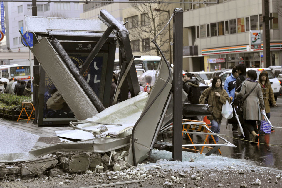 Photo - People walk past a ruined bus stop which was crushed by part of fallen outer wall of a nearby building in Sendai, Miyagi Prefecture (state) after Japan was struck by a strong earthquake off its northeastern coast Friday, March 11, 2011. (AP Photo/Kyodo News) JAPAN OUT, MANDATORY CREDIT, FOR COMMERCIAL USE ONLY IN NORTH AMERICA ORG XMIT: TOK817