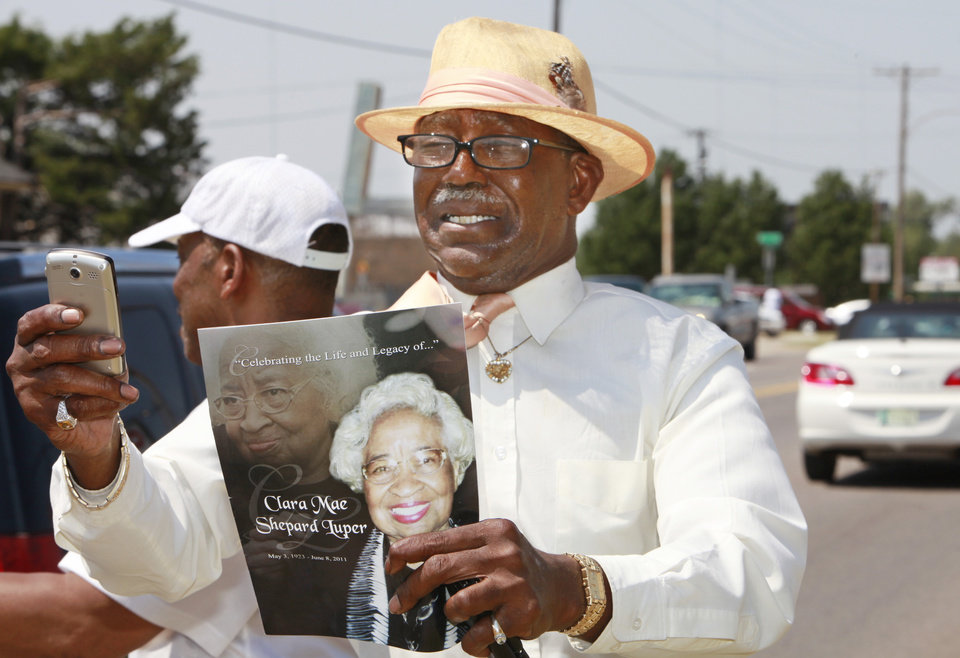 Orlando Cruse cries as he holds a program and takes photos of Clara Luper's funeral procession as it moves along Martin Luther King Avenue, Friday,  June 17, 2011.   Cruse was a history student of Luper's.    Photo by David McDaniel, The Oklahoman