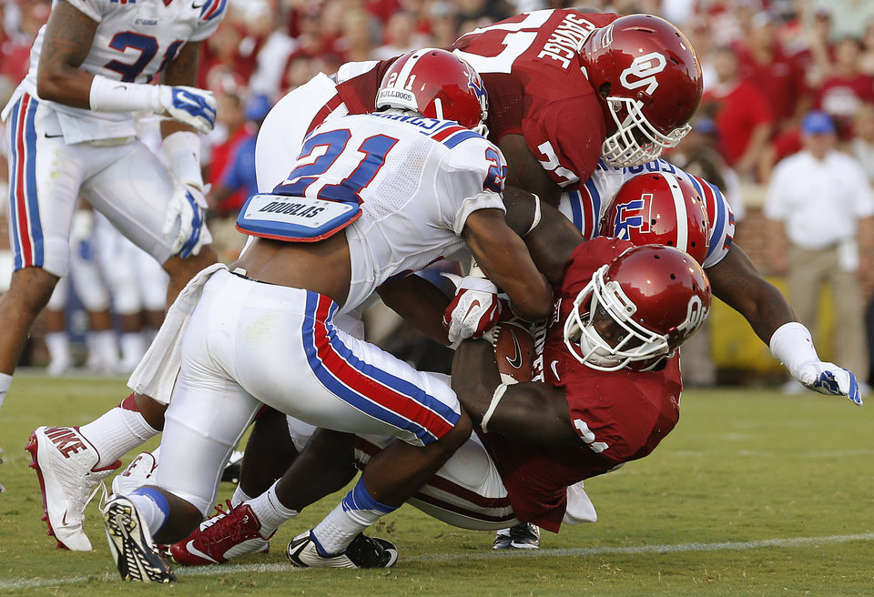 Photo - Oklahoma's Keith Ford (21) scores a touchdown as Louisiana Tech's Adairius Barnes (21) tries to bring him down during a college football game between the University of Oklahoma Sooners (OU) and the Louisiana Tech Bulldogs at Gaylord Family-Oklahoma Memorial Stadium in Norman, Okla., on Saturday, Aug. 30, 2014. Photo by Bryan Terry, The Oklahoman