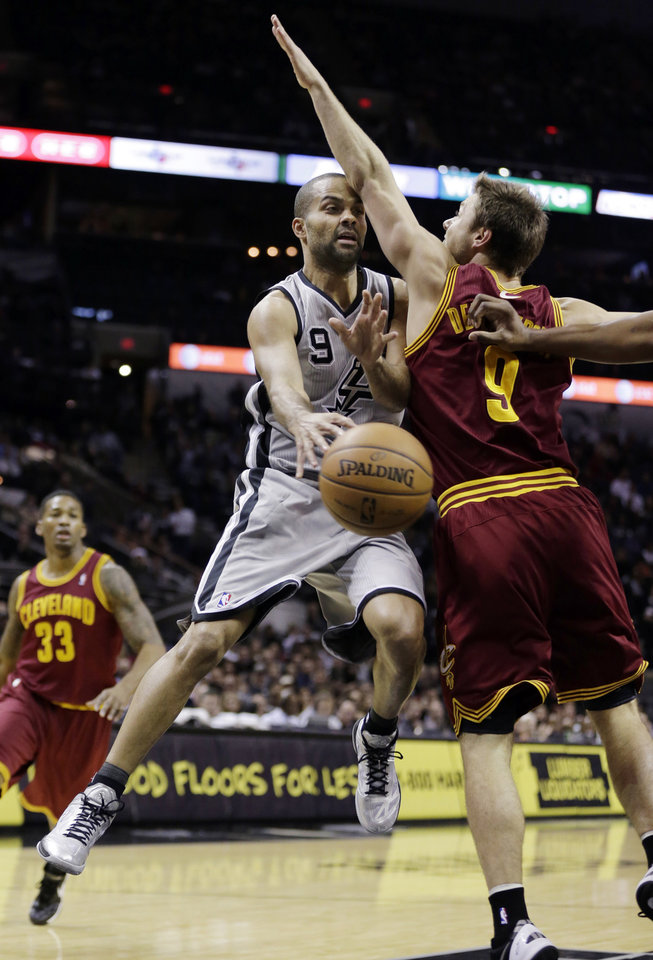 Photo - San Antonio Spurs' Tony Parker (9), of France, passes the ball around Cleveland Cavaliers' Matthew Dellavedova, right, during the first half of an NBA basketball game Saturday, Nov. 23, 2013, in San Antonio. (AP Photo/Eric Gay)