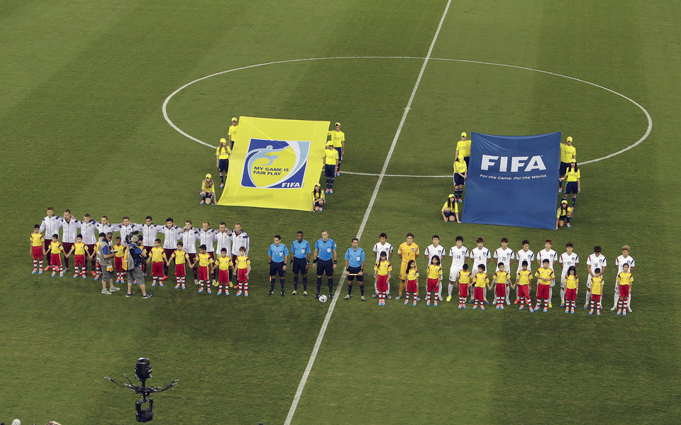 Photo - The players for Russia, left, and South Korea, right, line up prior to a group H World Cup soccer match at the Arena Pantanal in Cuiaba, Brazil, Tuesday, June 17, 2014. (AP Photo/Thanassis Stavrakis)