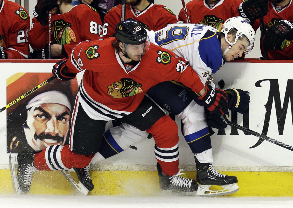 Photo - St. Louis Blues' Adam Cracknell, right, is checked by Chicago Blackhawks' Brandon Saad during the first period in Game 4 of a first-round NHL hockey playoff series in Chicago, Wednesday, April 23, 2014. (AP Photo/Nam Y. Huh)