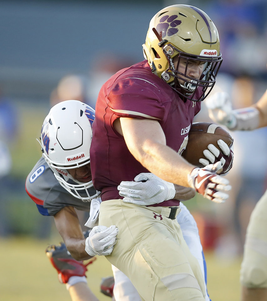 Photo - Cashion's Caden Harrell carries the ball as Jayden Tyson of Christian Heritage Academy tries to bring him down during a game in Cashion on Sept. 27. [Bryan Terry/The Oklahoman]