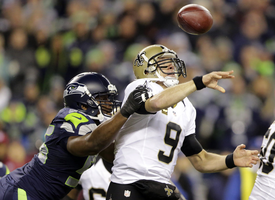 Photo - FILE - In this Dec. 2, 2013, file photo, Seattle Seahawks defensive end Cliff Avril hits the arm of New Orleans Saints quarterback Drew Brees causing a fumble that was returned for a touchdown by Seahawks defensive end Michael Bennett in the first half of an NFL football game in Seattle. The Seahawks finished the regular season as the best pass defense in the NFL with three All-Pro selections in the secondary. Their best performance came when they suffocated New Orleans in Week 13. Now comes the challenge of duplicating that in Saturday's NFC divisional playoff game against the Saints. (AP Photo/Scott Eklund, File)