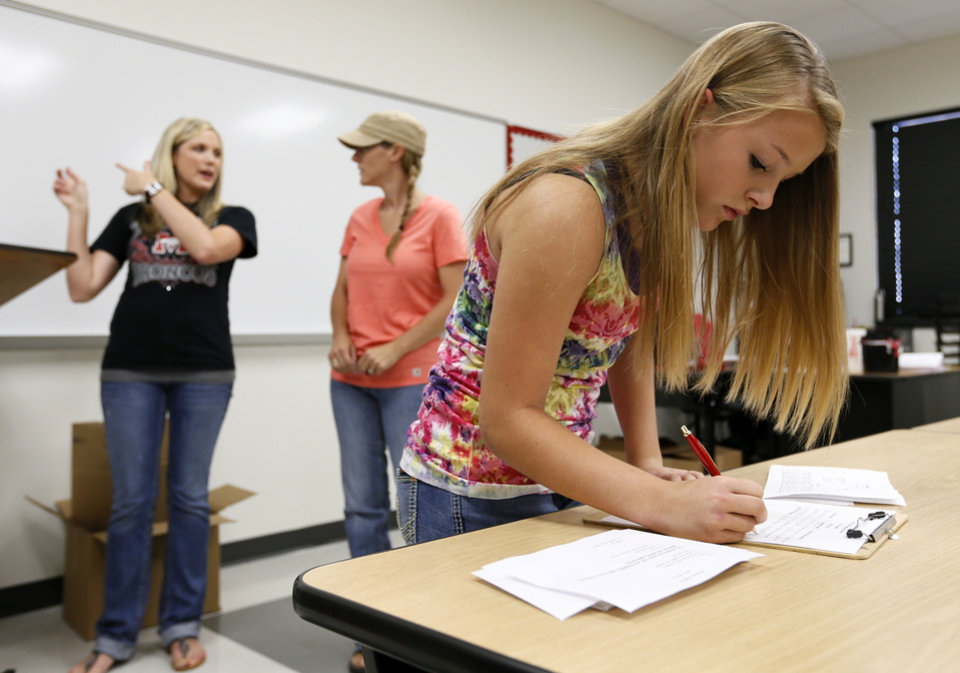 Freshman Payton Hegland fills out information for her ninth-grade biology teacher, Sharity Watts, back left, as Watts talks to Hegland�s mother, Carrie Hegland, during the Mustang High School open house.
