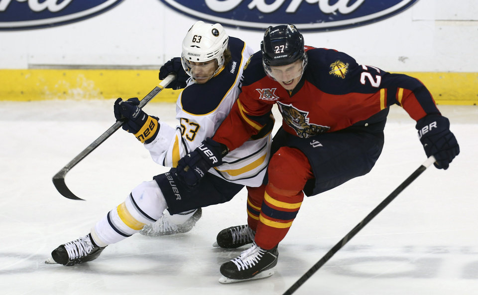 Photo - Buffalo Sabres' Tyler Ennis (63) and Florida Panthers' Nick Bjudstad (27) battle for the puck during the second period of an NHL hockey game in Sunrise, Fla., Friday, March 7, 2014. (AP Photo/J Pat Carter)