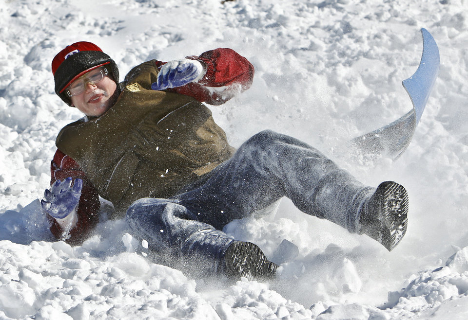 Photo - Saxon Green plows into the snow as he crashes at the bottom of the hill while sledding at Will Rogers Park on Wednesday, Feb. 2, 2011, Oklahoma City, Okla.   Photo by Chris Landsberger, The Oklahoman