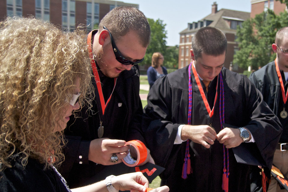 Dr. Heather Yates helps Chuck Major and Michael Lane decorate their caps before the Oklahoma State University graduation held in Gallagher Iba Arena in Stillwater, Oklahoma on May 5th, 2012. Photos by Mitchell Alcala for the Oklahoman