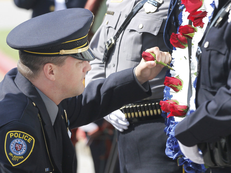 Photo - Oklahoma City Police Officer Chad Peery places a rose on a wreath during the Oklahoma Law Enforcement Officers Memorial Service in Oklahoma City, Friday, May  18,  2012. Photo By Steve Gooch, The Oklahoman
