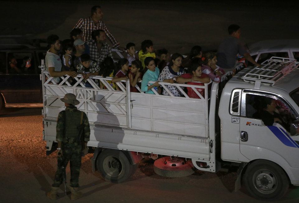 Photo - Fleeing Iraqi citizens from Mosul and other northern towns sit on a truck as they cross to secure areas at a Kurdish security forces checkpoint, in the Khazer area between the Iraqi city of Mosul and the Kurdish city of Irbil, northern Iraq, Wednesday June 25, 2014. Sunni insurgents who seized Iraq's second largest city attacked a nearby Christian village on Wednesday, bringing their fight closer to the largely Kurdish regions of northern Iraq which had remained so far largely untouched from the chaos sweeping the country. (AP Photo/Hussein Malla)