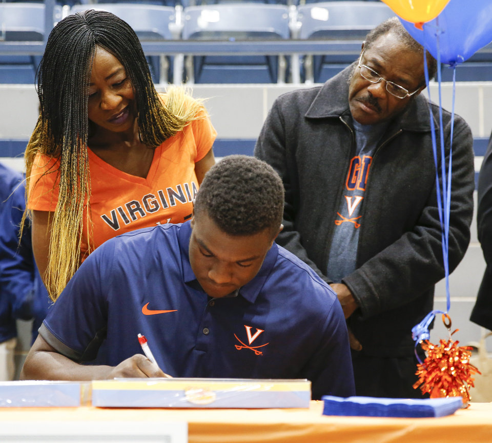 Photo - Daryl Dike signs to play soccer at Virginia as his parents, Jessy Dike and Vincent Dike, look on during a ceremony for National Signing Day at Edmond North High School in Edmond, Okla., Wednesday, Feb. 7, 2018. Photo by Nate Billings, The Oklahoman
