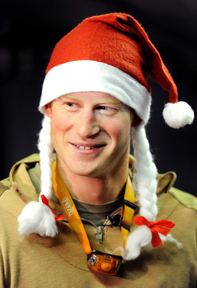 Photo - FILE - In this Dec. 12, 2012 file photo, Britain's Prince Harry wears a Santa hat as he shows a media crew his sleeping area at the VHR (very high readiness) tent, close to the flight-line, at Camp Bastion southern Afghanistan. During Prince Harry's 20-week deployment in Afghanistan, he served as an Apache helicopter pilot with the Army Air Corps. (AP Photo/ John Stillwell, Pool, File)