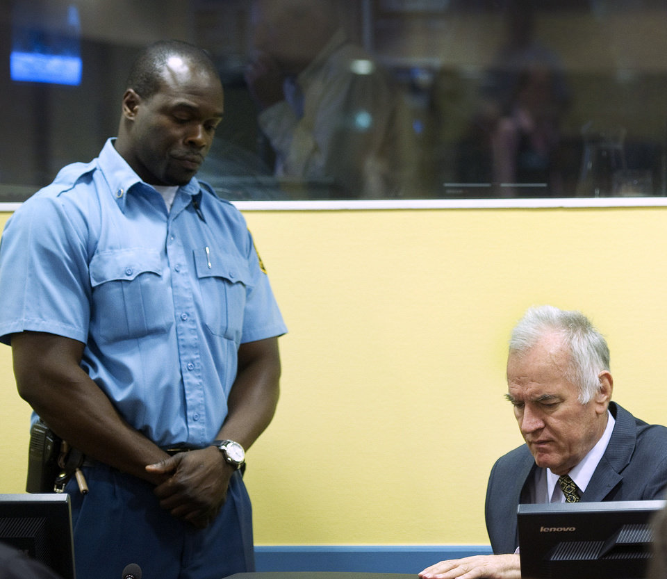 Photo -   Former Bosnian Serb military commander Gen. Ratko Mladic, right, and a UN security guard, left, are seen at the start of his trial at the Yugoslav war crimes tribunal in The Hague, Netherlands, Wednesday May 16, 2012. Twenty years after the opening shots of the Bosnian War, Mladic has gone on trial on charges of genocide, crimes against humanity and war crimes, his appearance at the UN tribunal marks the end of a long wait for justice to survivors of the 1992-95 war that left some 100,000 people dead. (AP Photo/Toussaint Kluiters, Pool)
