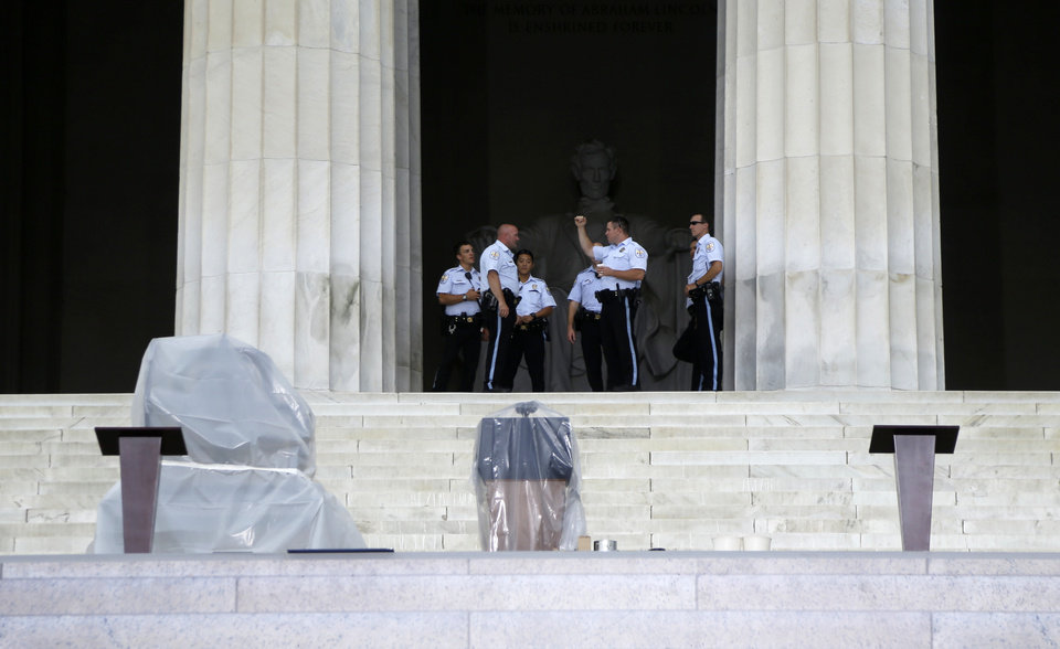 Plastic covers the podium on the steps of the Lincoln Memorial in Washington, Wednesday, Aug. 28, 2013, as security personnel gather before the Let Freedom Ring ceremony to commemorate the 50th Anniversary of the 1963 March on Washington for Jobs and Freedom. (AP Photo/Carolyn Kaster)