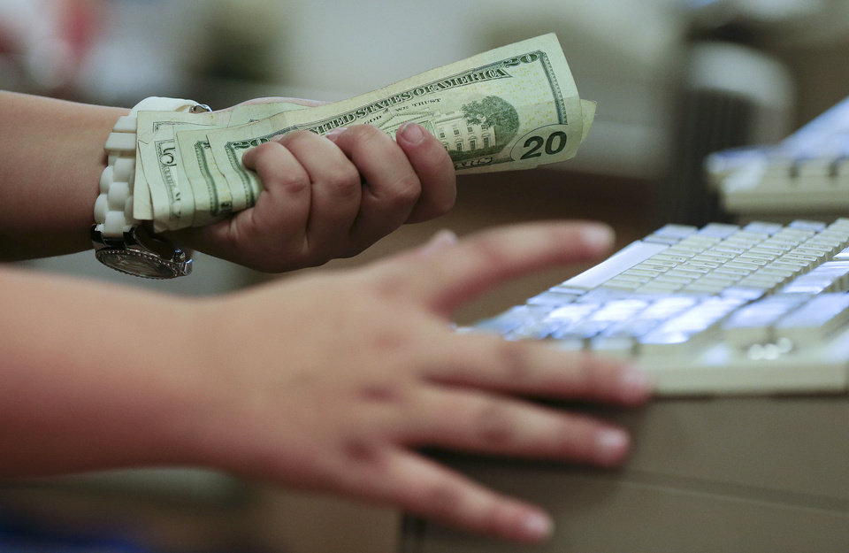 A cashier rings up a cash sale at a Sears store in Las Vegas in November. U.S. consumers borrowed more in November to buy cars and attend school, but stayed cautious with their credit cards, the Federal Reserve said Tuesday. AP PHOTO <strong>Julie Jacobson - AP</strong>