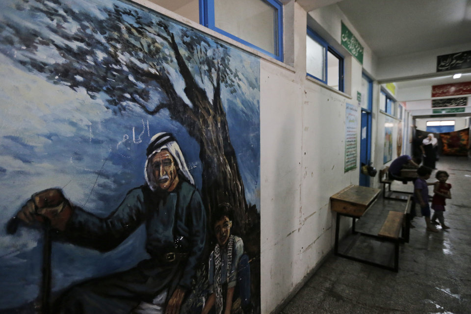 Photo - A painting depicting Palestinian rural life decorates a United Nations school where hundreds of families have sought refuge after fleeing their homes following heavy Israeli forces' strikes, in Jebaliya refugee camp, Gaza Strip, Friday, July 25, 2014. Over 140,000 Palestinians are seeking shelter in 83 UNRWA schools, according to UNRWA spokesman Chris Gunness. The number of Palestinians seeking shelter since the ground operation began has increased seven-fold. (AP Photo/Lefteris Pitarakis)