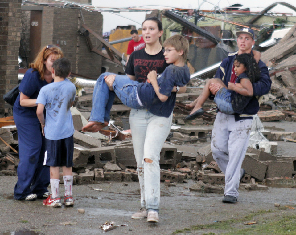 Teachers carry children away from Briarwood Elementary school after a tornado destroyed the school in south OKC Oklahoma City, OK, Monday, May 20, 2013. Near SW 149th and Hudson.  By Paul Hellstern, The Oklahoman