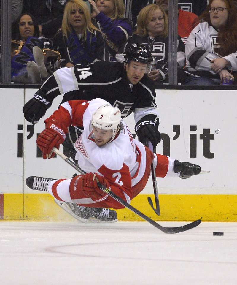 Photo - Detroit Red Wings defenseman Brendan Smith, below, falls as he passes the puck under pressure from Los Angeles Kings right wing Justin Williams during the first period of an NHL hockey game, Saturday, Jan. 11, 2014, in Los Angeles. (AP Photo/Mark J. Terrill)