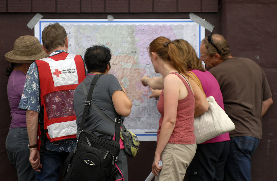 Photo -   Evacuees of the Waldo Canyon Fire look at the most recent map of the fire's progression at the Cheyenne Mountain High School evacuation center on Wednesday, June 27, 2012, in Colorado Springs, Colo. The wildfire doubled in size overnight to about 24 square miles (62 square kilometers), and has so far forced mandatory evacuations for more than 32,000 residents. (AP Photo/Bryan Oller)