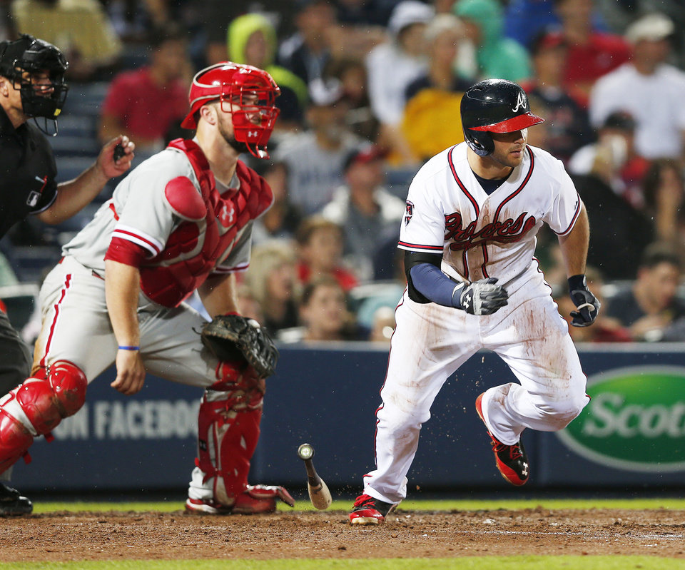 Photo - Atlanta Braves' Tommy La Stella (7) runs after hitting an RBI single in front of Philadelphia Phillies catcher Cameron Rupp during the fifth inning of a baseball game in Atlanta, Friday, July 18, 2014. (AP Photo/John Bazemore)