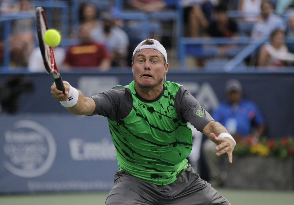 Photo - Lleyton Hewitt, of Australia, reaches for the ball during a game against Milos Raonic, of Canada, at the Citi Open tennis tournament, Thursday, July 31, 2014, in Washington. (AP Photo/Luis M. Alvarez)