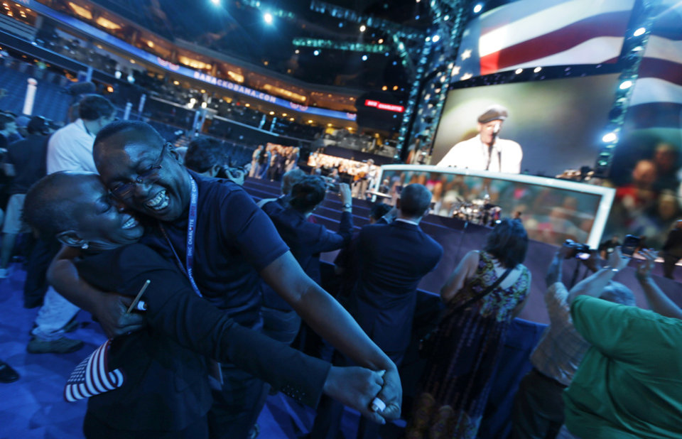 Photo -   North Carolina delegates Denise Adams, left, and Charles Evans dance on the floor as musician James Taylor sings,