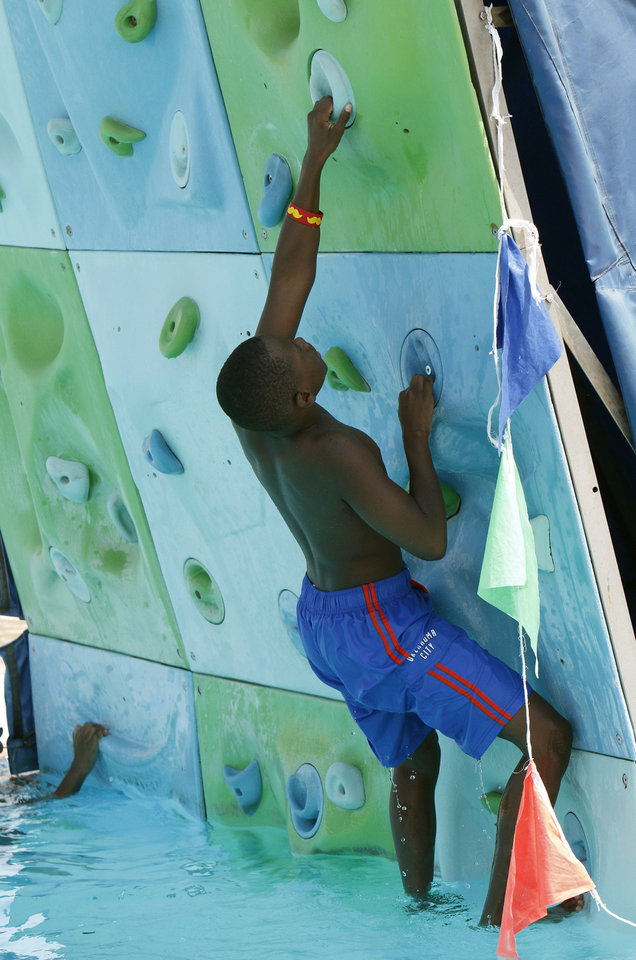 Photo -  Tristan Peters, 9, attempts to scale the climbing wall at Pelican Bay Aquatic Center in Edmond. Photo by Paul Hellstern, The Oklahoman   PAUL HELLSTERN -