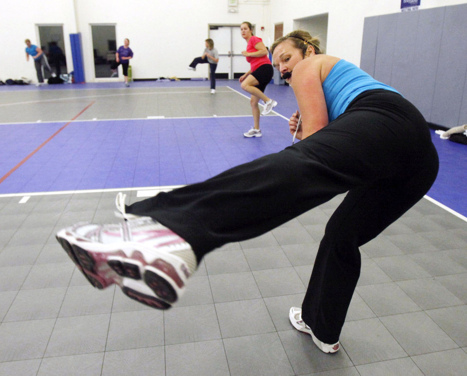 Photo - Instructor Kerri Collison leads exercises during a New Year's Boot Camp at the Holy Trinity Lutheran Church in Edmond, OK, Saturday, Jan. 2, 2010. By Paul Hellstern, The Oklahoman ORG XMIT: KOD