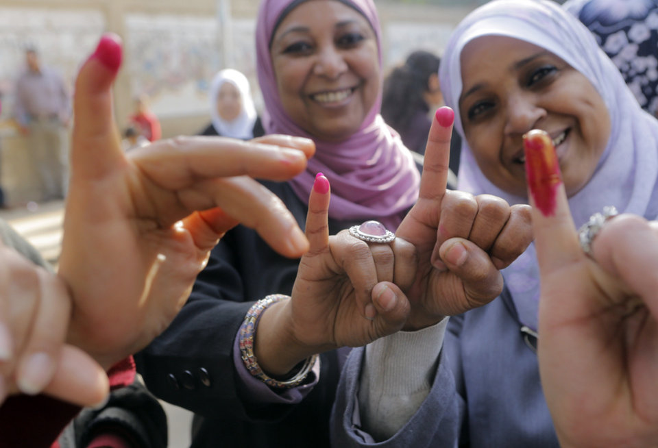 Photo - Egyptians women show their inked fingers after casting their votes at a polling station in Cairo, Egypt, Tuesday, Jan. 14, 2014. Egyptians are voting on a draft for their country's new constitution that represents a key milestone in a military-backed roadmap put in place after President Mohammed Morsi was overthrown in a popularly backed coup last July. (AP Photo/Amr Nabil)