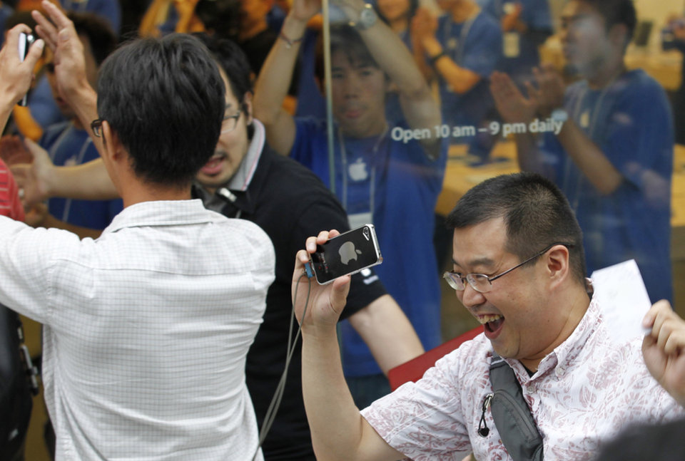 Photo -   Customers celebrate as Apple Inc. started selling iPhone 5 at a store in Tokyo Friday morning, Sept. 21, 2012. Apple's Asian fans jammed the tech juggernaut's shops in Australia, Hong Kong, Japan and Singapore to pick up the latest version of its iPhone. (AP Photo/Koji Sasahara)