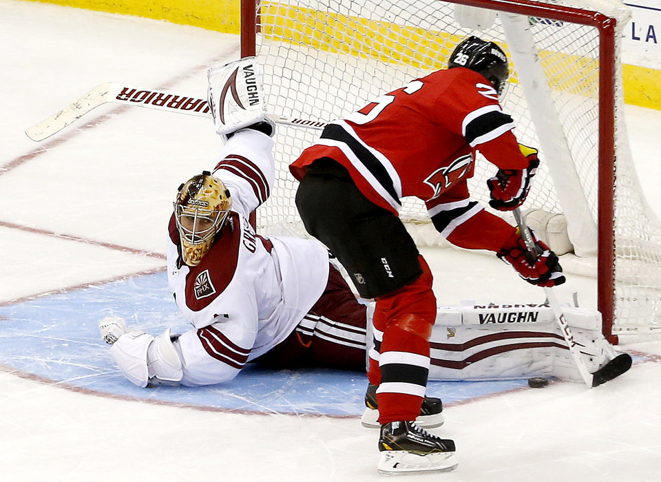 Photo - Phoenix Coyotes goalie Thomas Greiss, left, of Germany, blocks a shot by New Jersey Devils left wing Patrik Elias, of the Czech Republic, during a shootout in an NHL hockey game, Thursday, March 27, 2014, in Newark, N.J. The Coyotes won 3-2. (AP Photo/Julio Cortez)