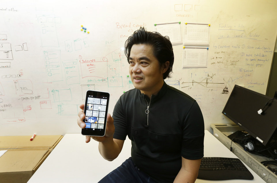 "Photo - In this photo taken July 3, 2014, Albert Shum, who heads interaction design across a range of Microsoft products including personal computer operating systems, Xbox game consoles, and phones, poses with a Windows phone in front of a whiteboard used to brainstorm ideas, at the Windows Design Studio in Redmond, Wash. A former designer for shoemaker Nike, Shum was part of the team that revolutionized the Windows Phone design to feature the boxy, so-called ""live tiles"" that are central to the touch-based interface in Windows 8. (AP Photo/Ted S. Warren)"