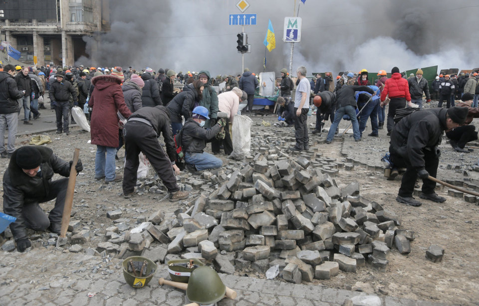 Photo - Protesters dig for stones during clashes with riot police in Kiev's Independence Square, the epicenter of the country's current unrest, Kiev, Ukraine, Wednesday, Feb. 19, 2014. The deadly clashes in Ukraine's capital have drawn sharp reactions from Washington, generated talk of possible European Union sanctions and led to a Kremlin statement blaming Europe and the West. A roundup of some of the international reactions. (AP Photo/Efrem Lukatsky)