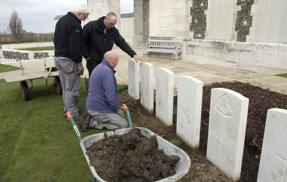 Photo - A group of workers for the Commonwealth War Graves Commission discuss the removal of a row of damaged WWI headstones at Tyne Cot cemetery in Zonnebeke, Belgium on Monday, April 15, 2013. With nearly 12,000 graves the cemetery is the largest Commonwealth war cemetery in the world in terms of burials. The damaged headstones will be removed and replaced with newly engraved stones in preparation for the upcoming centenary which begins in 2014. (AP Photo/Virginia Mayo)