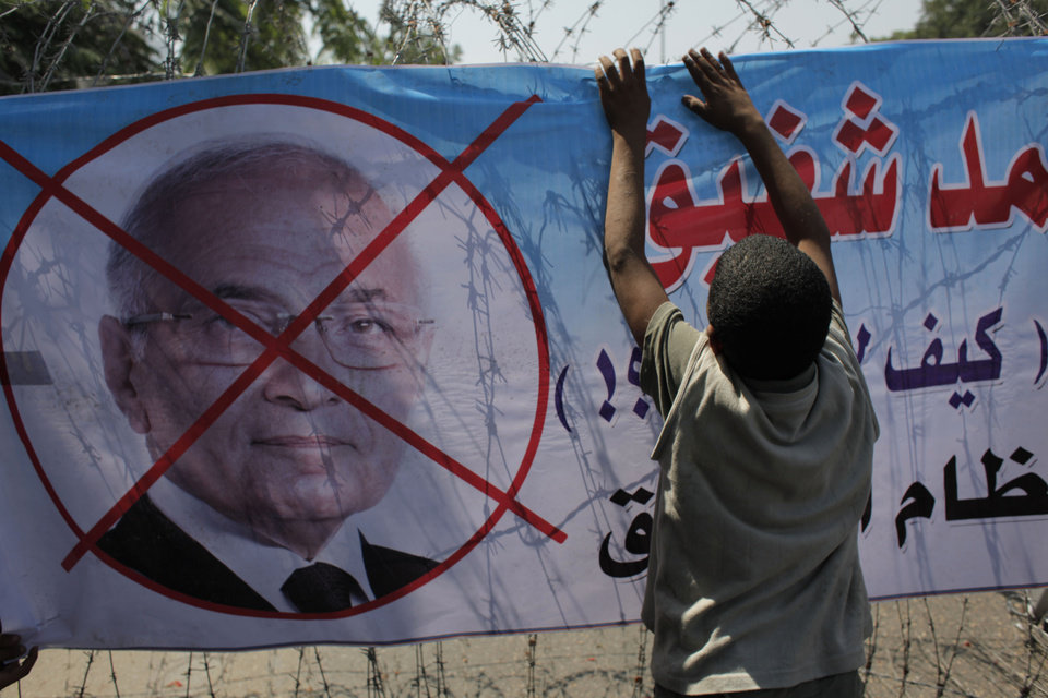 Photo -   An Egyptian youth hangs a banner with a defaced picture of presidential candidate, Ahmed Shafiq and Arabic that reads