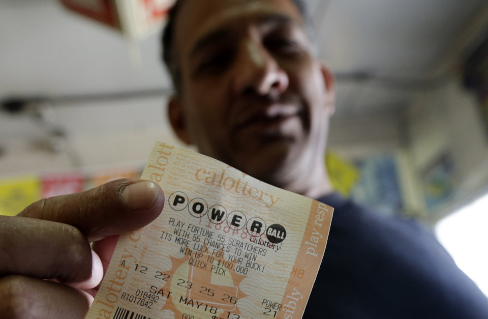 Photo - Joe Fajardo poses holding his Powerball lottery ticket after buying it at a store Saturday, May 18, 2013, in the Barrio Logan neighborhood of San Diego. With the majority of possible combinations of Powerball numbers in play, someone is almost sure to win the lottery game's highest jackpot on Saturday night, a windfall of hundreds of millions of dollars — and that's after taxes. (AP Photo/Gregory Bull)