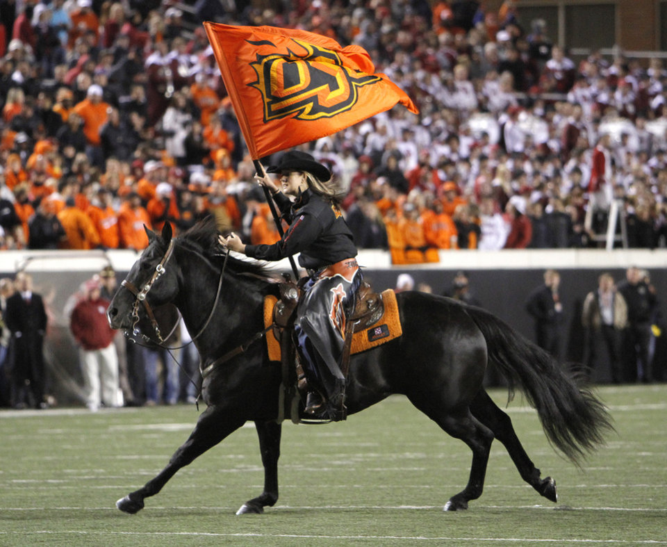 Photo - Bullet runs onto the field during the Bedlam college football game between the University of Oklahoma Sooners (OU) and the Oklahoma State University Cowboys (OSU) at Boone Pickens Stadium in Stillwater, Okla., Saturday, Nov. 27, 2010. Photo by Chris Landsberger, The Oklahoman
