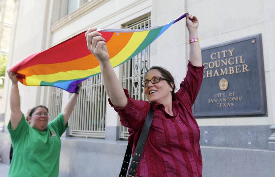 Photo - Julie Pousson, right, and Jennifer Echeverry, left, celebrate after a non-discrimination ordinance was passed by the San Antonio city council, Thursday, Sept. 5, 2013, in San Antonio. The ordinance in part will prohibit discrimination based on sexual orientation and gender identity. (AP Photo/Eric Gay)