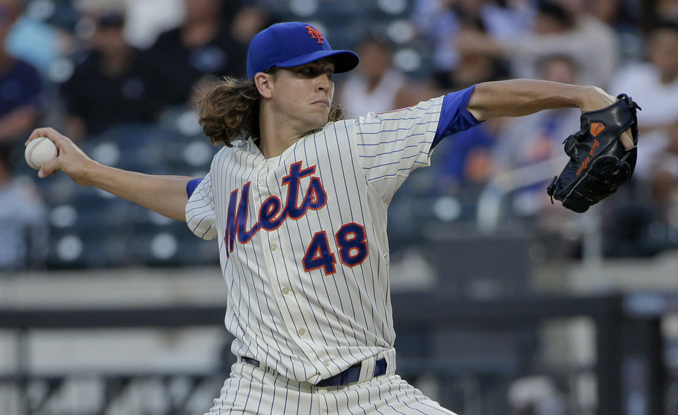Photo - New York Mets pitcher Jacob deGrom  delivers against the Atlanta Braves in the first inning of a baseball game, Tuesday, July 8, 2014, in New York. (AP Photo/Julie Jacobson)