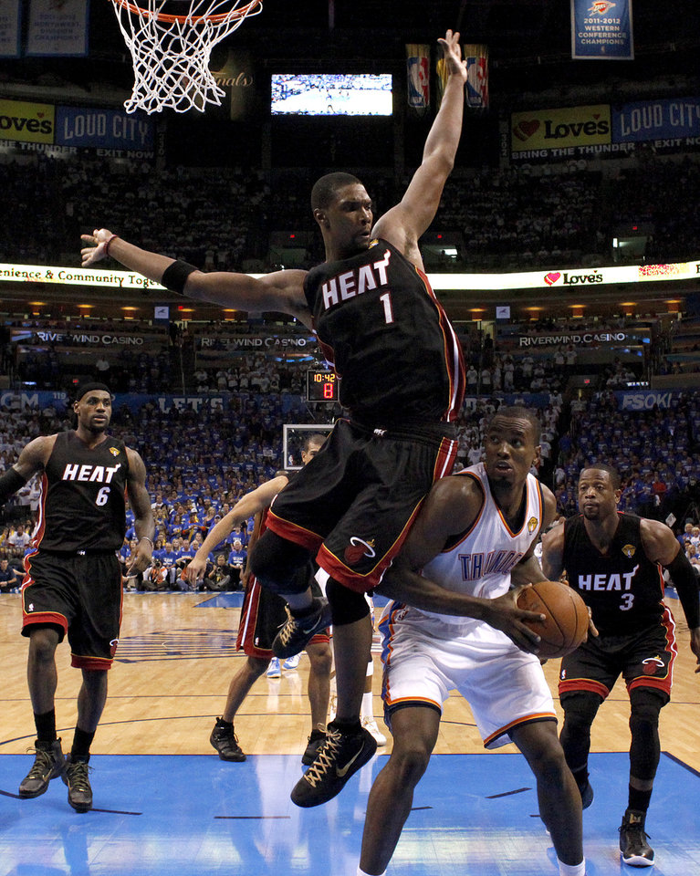 Photo - Oklahoma City's Serge Ibaka (9) is defended by Miami's Chris Bosh (1) during Game 2 of the NBA Finals between the Oklahoma City Thunder and the Miami Heat at Chesapeake Energy Arena in Oklahoma City, Thursday, June 14, 2012. Photo by Sarah Phipps, The Oklahoman