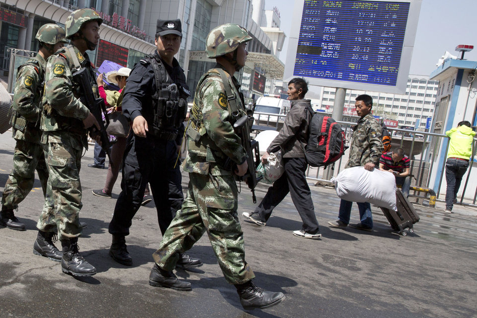 Photo - Heavily armed Chinese paramilitary policemen march past the site of the Wednesday's explosion outside the Urumqi South Railway Station in Urumqi in northwest China's Xinjiang Uygur Autonomous Region Thursday, May 1, 2014. Chinese President Xi Jinping has demanded 'decisive actions