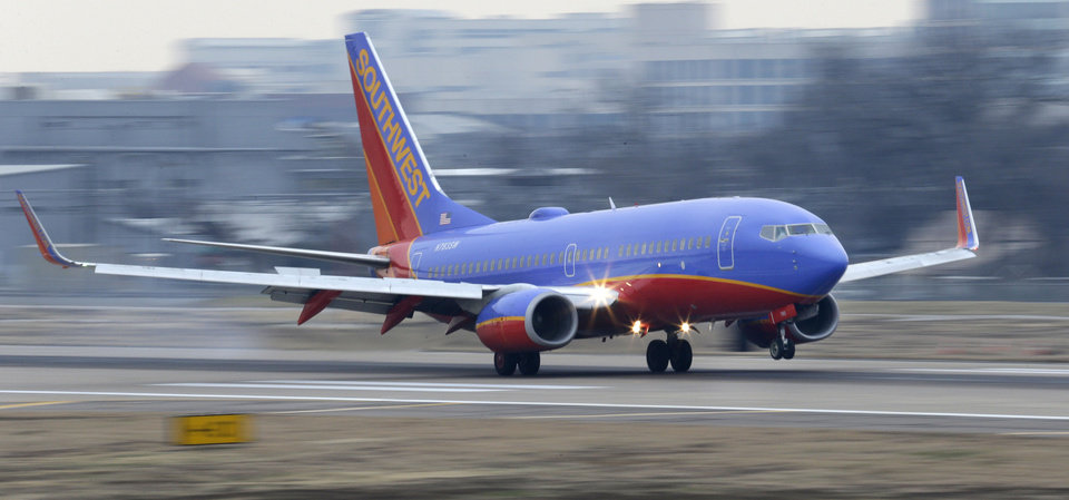 A Southwest  Airlines jet plane lands at Love Field Monday, Feb. 3, 2014, in Dallas. Southwest Airlines plans to start nonstop flights between Dallas and New York and 14 other cities this fall, when federal limits on the airline's home airport end. (AP Photo/LM Otero)