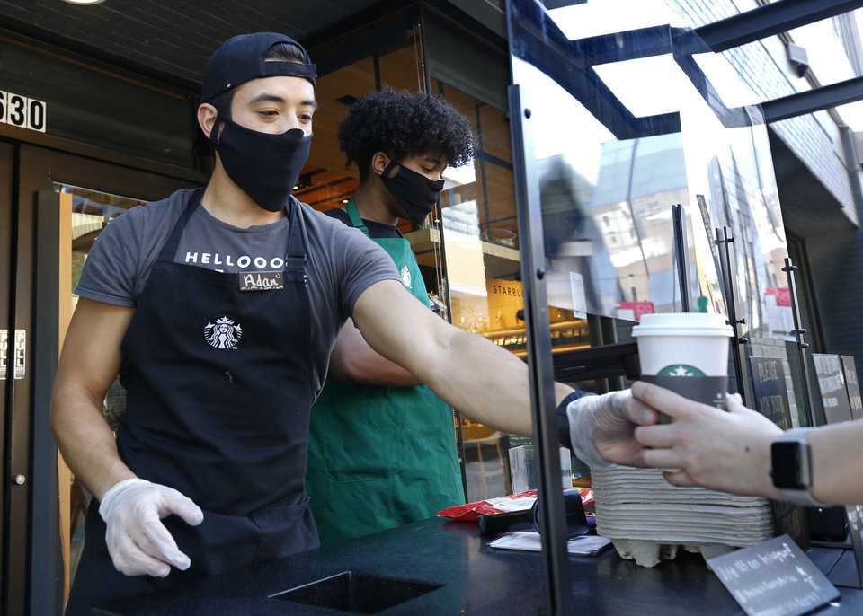 Photo - Starbucks shift supervisor Adan Miranda wears a face mask as he serves a drink to a customer while standing behind a plexiglass shield in a booth outside the store in Sacramento, Calif., Thursday, May 21, 2020. [AP Photo/Rich Pedroncelli]