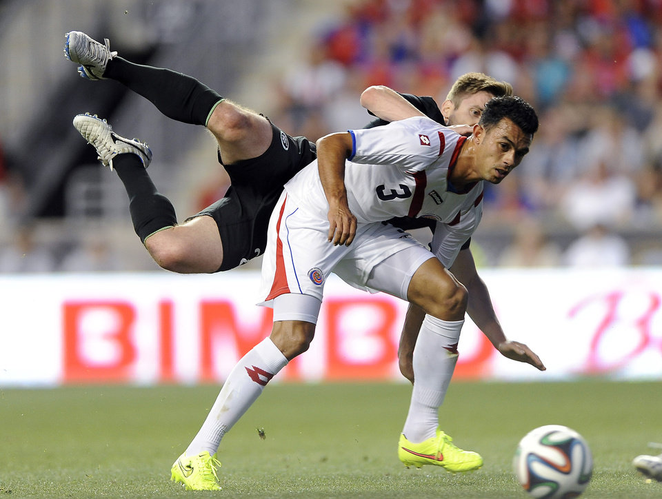 Photo - Ireland's Kevin Doyle turns the ball over and collides with Costa Rica's Giancarlo Gonzalez (3) during the first half of an international friendly soccer match on Friday, June 6, 2014, in Chester, Pa. (AP Photo/Michael Perez)