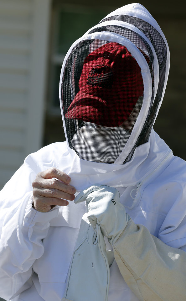 Tricia Harvey adjusts protective gear before Brian Royal demonstrates bee keeping techniques to the Noble Bee Keepers Club at his home based business on Saturday, May 4, 2013, in Norman, Okla.  